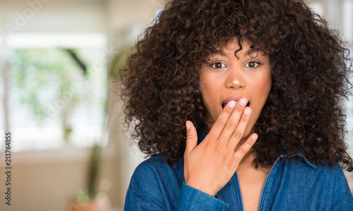 Leinwandbild Motiv African american woman cover mouth with hand shocked with shame for mistake, expression of fear, scared in silence, secret concept