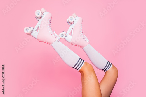 Close up crop photo of  legs in vintage quad roller skates shoes isolated on pink background - 213781894