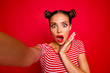 Leinwandbild Motiv OOPS! Self portrait of cute, trendy and shocked woman with bun hairdo wide open eyes mouth shooting selfie on front camera isolated on red background