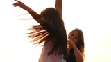 Beautiful young women whirling on the pylon against the sky outdoors - 213784441
