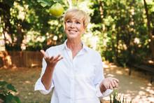 """Постер, картина, фотообои """"Cheerful mature woman holding green apple"""""""
