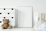 Mockup of white empty poster between cradle and teddy bear in kid's room interior. Real photo - 213798635