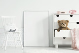 Teddy bear and pink blanket in cabinet next to empty poster with mockup in baby's room interior. Real photo - 213798679