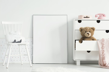 Teddy bear and pink blanket in cabinet next to empty poster with mockup in baby's room interior. Real photo © Photographee.eu