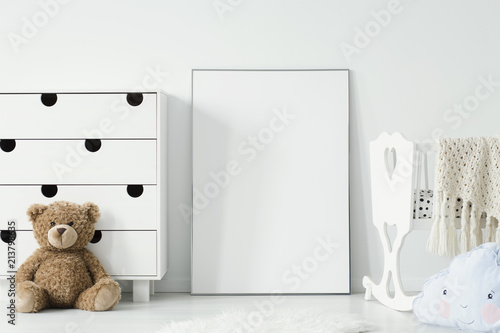 Mockup of white empty poster between cradle and teddy bear in kid's room interior. Real photo