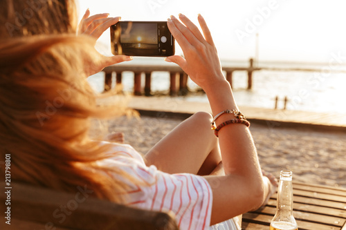 Side view of a young girl in summer clothes taking a picture