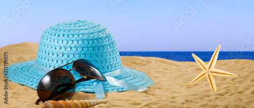 glasses, hat and sea shells on the sand