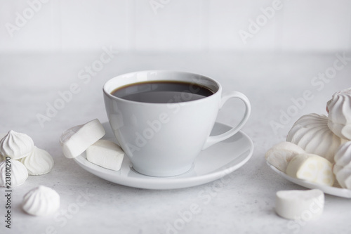 Cup of coffee on white background. Marshmallows and sweets.