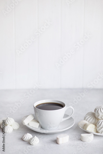 Cup of coffee on white background. Marshmallows, sweets and coffee beans.