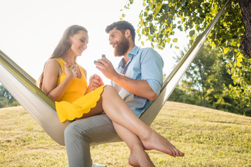 Side low-angle view of a cheerful young man making a marriage proposal to his beautiful girlfriend, while swinging together in a hammock outdoors in a summer day © Kzenon