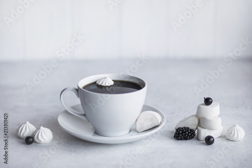 Cup of coffee, white background. Marshmallows, blue, black berries. Blueberries, blackberries, black currants.