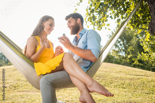 Side low-angle view of a cheerful young man making a marriage proposal to his beautiful girlfriend, while swinging together in a hammock outdoors in a summer day