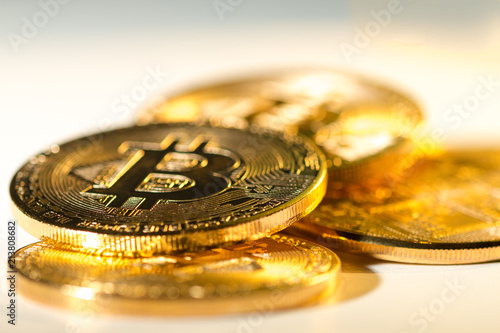 Golden Bitcoins heap on white background with copy space.