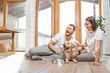 Young lovely couple in white t-shirts playing with their dog sitting on the floor in the house