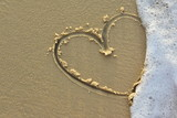 heart on a sand of beach with wave on background - 213814611