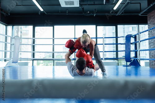Foto Murales Old friend. Blonde-haired female boxer feeling happy and satisfied while fighting her old friend in gym