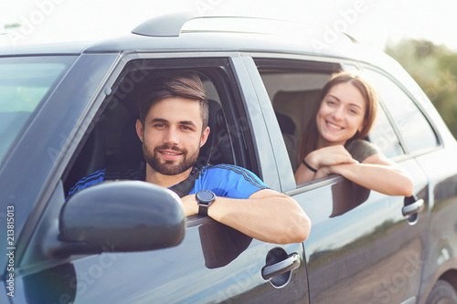 Foto Murales Happy couple traveling by car on the road in the summer.