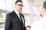 Portrait of serious executive in glasses listening to employee. Young Caucasian manager with coffee cup talking to colleague. Meeting concept - 213815451