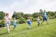 Leinwanddruck Bild - Man with child playing football outside on field
