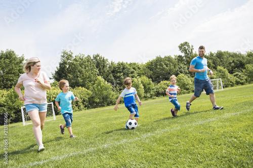Leinwanddruck Bild Man with child playing football outside on field