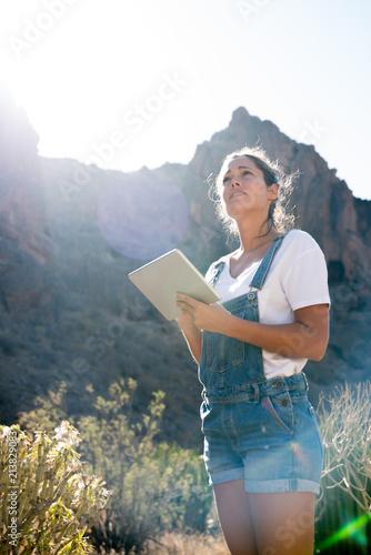 Fototapeta Woman standing in long grass looking down