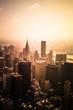View of buildings across New York City skyline under golden sunset light - 213832424