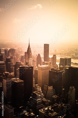 Fototapeta View of buildings across New York City skyline under golden sunset light