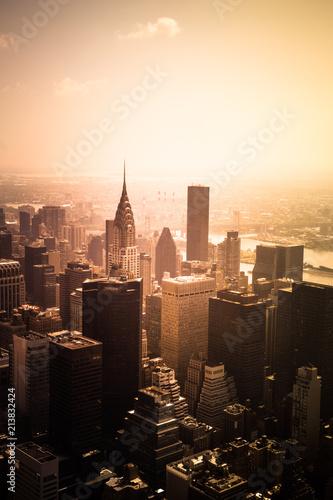 Foto Murales View of buildings across New York City skyline under golden sunset light