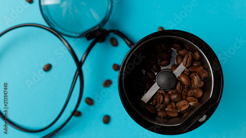 Electric coffee grinder with roasted coffee beans on the kitchen table with blue tabletop. Top view