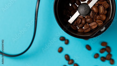 Electric coffee grinder with roasted coffee beans on the kitchen table with blue tabletop. Top view. Close-up