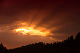 Dramatic dark red sun rays through the clouds. - 213849840