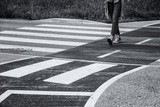 Pedestrian walks on asphalt road. Monochrome filter effect used. - 213850607