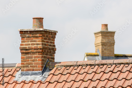 Brick chimney stack on modern contemporary house roof top - 213859409