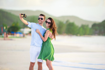 Happy couple taking a photo on white beach on honeymoon holidays