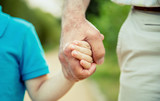 Child holding hand of senior man over a nature background. Two different generations concept. - 213906221