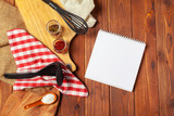 Blank sheet of opened notepad and kitchen utensils on  table with tablecloth, copy space - 213909009