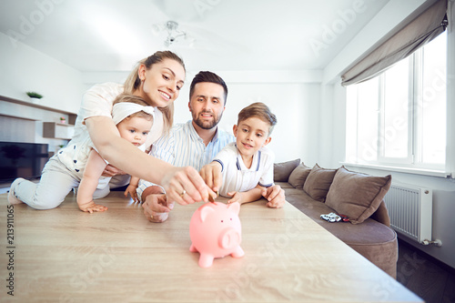 Leinwandbild Motiv A smiling family saves money with a piggy bank. Happy family at the table in the room.