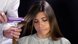 Beautiful woman bored while hairdresser is straightening her long hair - 213921469