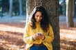 Casual cheerful young woman texting on her smartphone outdoor in autumn at city park.