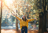 Casual joyful woman having fun throwing leaves in autumn at city park. - 213922220