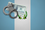 Guatemala flag  with handcuffs and a bundle of dollars. The concept of breaking the law and thieves crimes