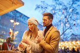 A beautiful young couple smiling and checking the gifts in a christmas market. - 213935608