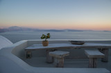 Whitewashed House on Cliff with Sea View, Wooden Table and Tiny Orange Tree during Sunset in Oia, Santorini, Cyclades, Greece - 213935874