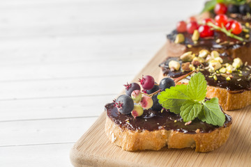 Sandwiches with chocolate paste, pistachio nuts and fresh berries on a wooden serving Board. Copy space