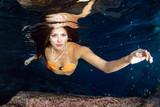 Mermaid swimming underwater in the deep blue sea - 213951484