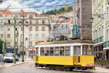 Vintage Yellow tram in the city center of Lisbon in a beautiful summer day, Lisbon, Portugal.