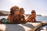 Three young women sunbathing on yacht - 213966698