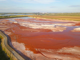 Aerial view of a reservoir full of red toxic sludge - 213967056