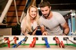 Quadro Couple playing table football in night bar