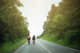 Two cyclists riding bicycles uphill in rural area in Thailand
